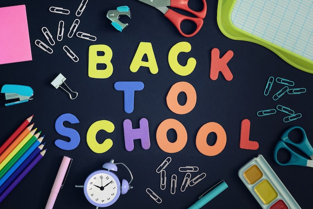 컬러 문자와 검은 배경의 중심에 줄 지어 비문 다시 학교로.