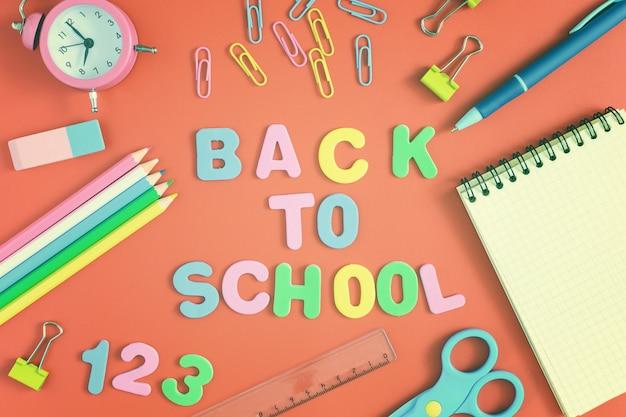 밝은 주황색 배경의 중앙에는 back to school이라는 비문이 컬러 문자로 만들어져 있습니다. 근처에는 다채로운 학교 및 사무용품이 있습니다.