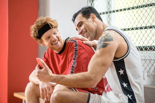 В раздевалке. два баскетболиста сидят в раздевалке и разговаривают