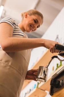 コーヒーショップで。コーヒーマシンの近くに立って、コーヒーを準備しながらカップを持っている素敵なプロの快適なバリスタ