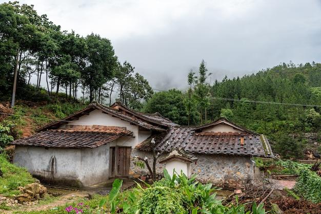 雨上がりの田園地帯では、森や家が濡れています