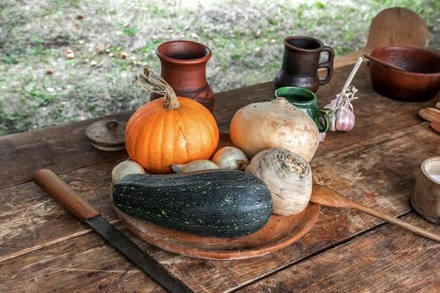 안뜰에는 야채와 골동품 요리가있는 나무 테이블이 있습니다.
