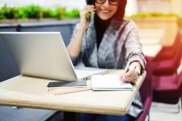 コワーキングで。ノートパソコンで作業しながら電話で話している、スマートカジュアルな服を着た陽気な女性の側面写真。