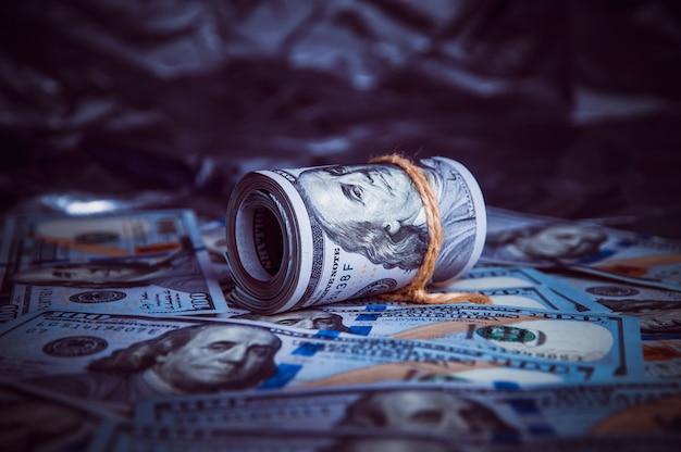 В темноте на разбитых деньгах лежит рулон долларов.