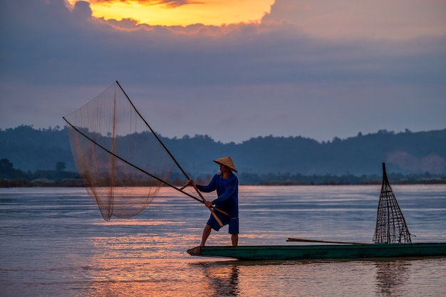 日の出前の早朝、木製のボートに乗ったアジアの漁師が、自然の川で淡水魚を捕まえるための網を投げました。
