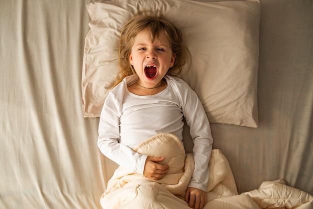 Рано утром девочка лежит в постели и яростно зевает, ее рот открыт