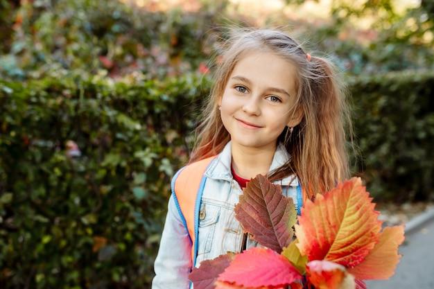 秋、7歳の女の子が学校に行き、手を振る