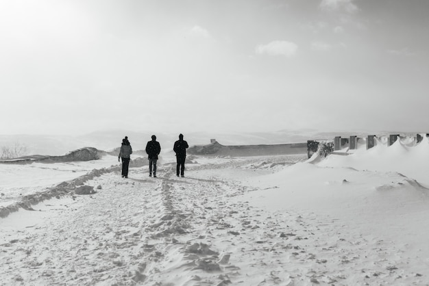 추운 북쪽 눈 덮인 들판을 걷는 세 사람