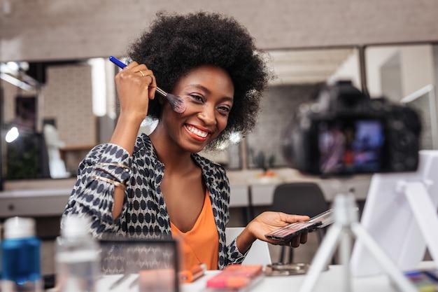 ファッションスタジオにて。座ってビデオ レッスンを行う巻き毛の肯定的な浅黒い肌の女性