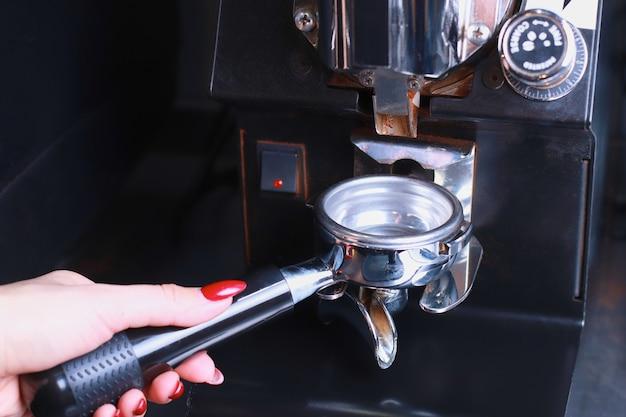 В женской руке подставка для кофе, кофейные зерна переливаются в фильтр.
