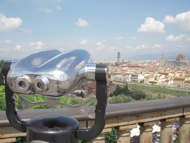 前景にはコイン式望遠鏡があり、背景にはイタリアのフィレンツェの街の景色が見えます。