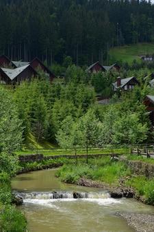 手前には、泥水と小さな滝が流れる川が流れています。その後ろには、緑の木々の後ろの山の近くにあるホテルの家が見えます。