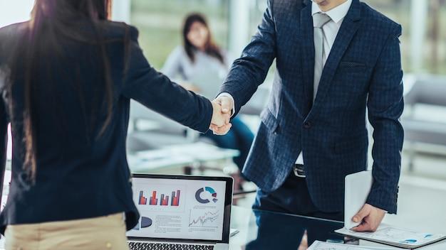フォアグラウンドでは、現代のオフィスの職場の近くで金融パートナーと握手しています