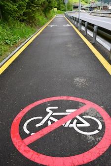 手前のアスファルト歩道には、サイクリストの乗車を禁止する標識があります。バックグラウンドで、遠近法で、空のジョギングトラックを残す