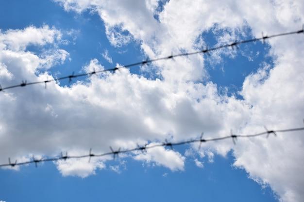 전경에는 흰 구름과 함께 밝은 푸른 하늘을 배경으로 두 줄의 철조망이 있습니다. 와이어가 초점이 많이 맞지 않음
