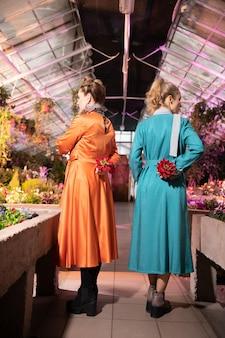 温室内。ポーズをとりながら花の間に立つ魅力的な若い女性