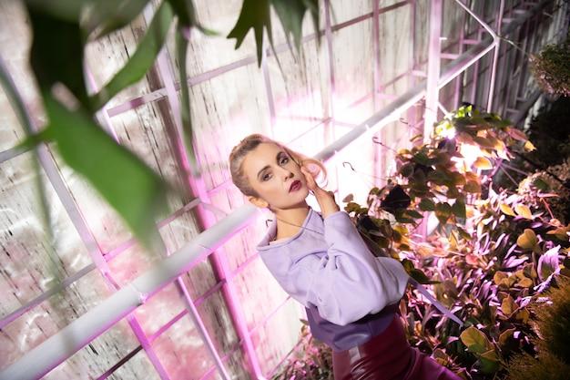 温室内。植物の間に立って頬に触れる真面目な魅力的な女性