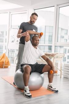 В тренажерном зале. симпатичный молодой человек с использованием спортивного инвентаря во время тренировки с личным тренером
