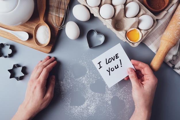メモの手で私はあなたを愛しています。灰色の背景に自家製クッキーを作るための材料。バレンタインデー、父の日、母の日のお菓子を作るというコンセプト。フラットレイ、上面図。