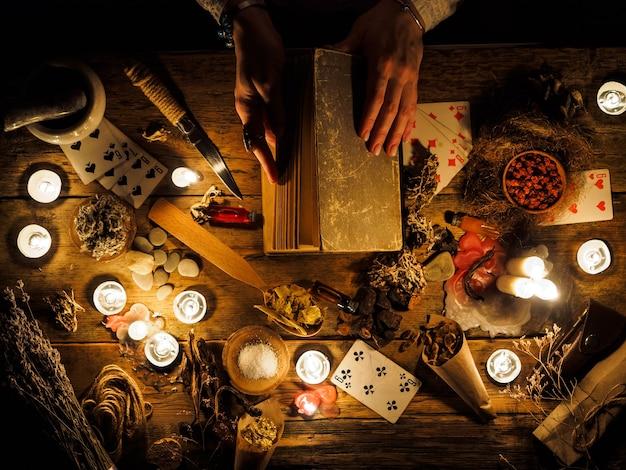 В руках гадалки старая книга с заклинаниями.