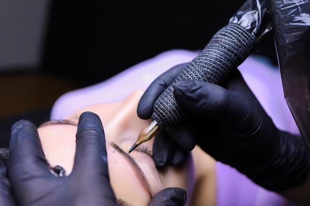 黒い手袋をはめたマスターの手にはタトゥーマシンがあり、クライアントの眉毛のタトゥーを入れています。