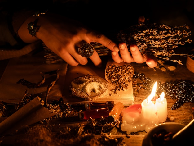 В руках ведьм букет сухих трав для гадания. свет от свечей на старом волшебном столе. атрибуты оккультизма и магии.