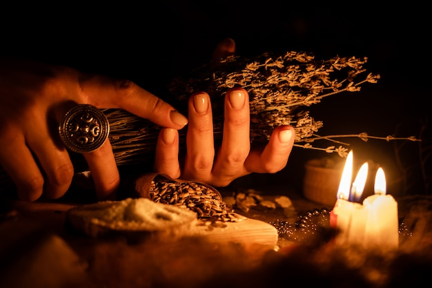 占いのために乾燥したハーブの束を魔女の手に。古い魔法のテーブルのキャンドルからの光。オカルティズムと魔法の属性。