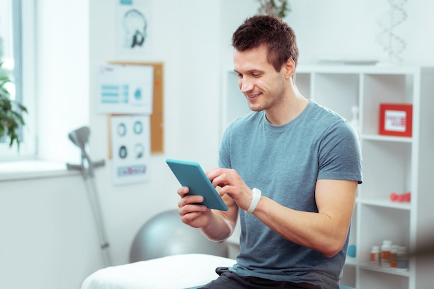병실에서. 병실에서 의사를 기다리는 동안 자신의 태블릿을 사용하는 긍정적 인 젊은 남자