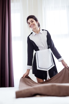 ホテルの部屋で。ホテルの部屋のベッドの近くに立って笑っている陽気な素敵な女性