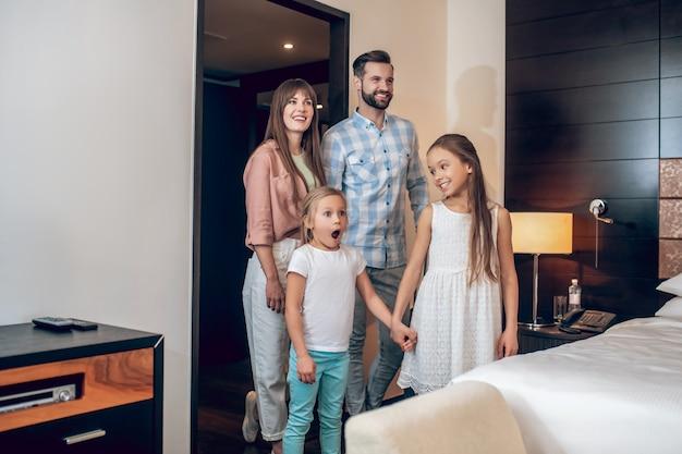 В отеле. молодая милая семья стоит в комнате и выглядит взволнованной