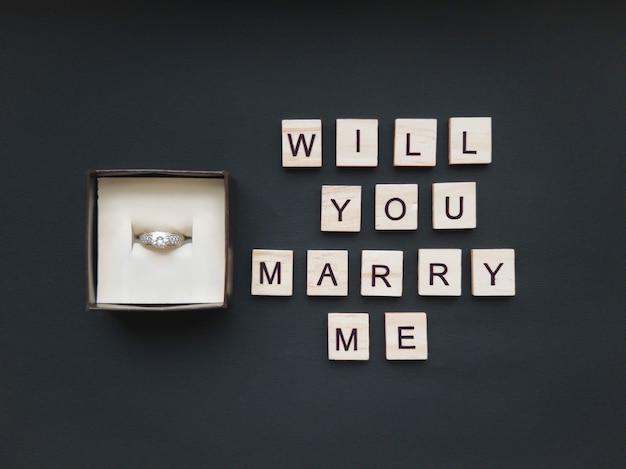 В шкатулке для украшений кольцо с камнем и надпись из деревянных квадратов на красивом черном фоне. романтическая концепция. плоский стиль.