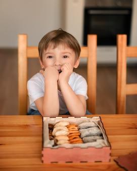 台所では、リンゴ、桃からなるドライフルーツの箱の前に男の子が座っています。