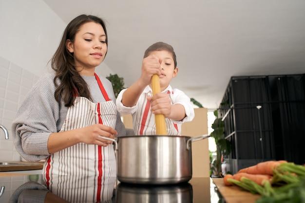 부엌에서 한부모 가족이 함께 파스타를 요리하고 있는 엄마와 아들이 파스타를 끓이고 있다