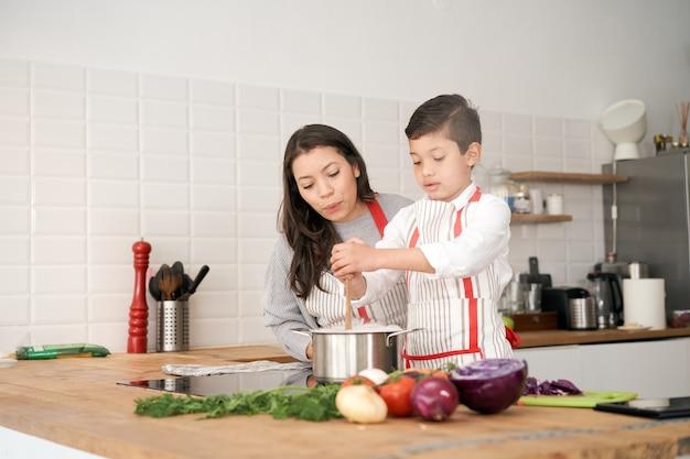 キッチンでは、一人親家庭が母と息子が一緒にパスタを鍋でかき混ぜながらパスタを調理しています...