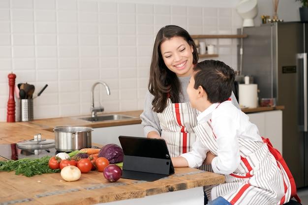 キッチンで息子がタブレットの子供たちを介してオンラインで料理レシピを検索し、両親を助けています...