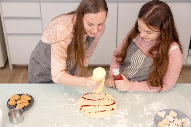 На кухне дома игривая мать и дочь кричат, готовя тесто для пиццы.