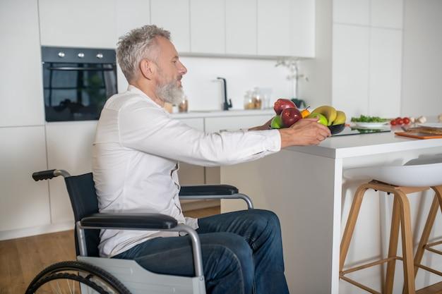 부엌에서. 부엌에서 아침 식사를 준비하는 회색 머리 장애인
