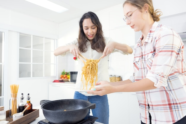 На кухне две счастливые молодые сестры-близнецы готовят спагетти на обед.