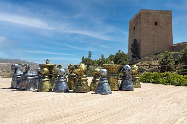 В средневековом замке лорка испания гигантские шахматы на платформе с видом на оборонительную башню