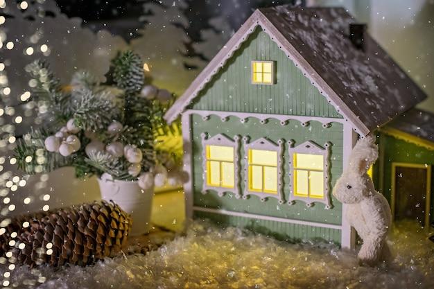 В середине зимнего пейзажа игрушечный зайчик стоит у лампы в виде деревенского домика и елки.