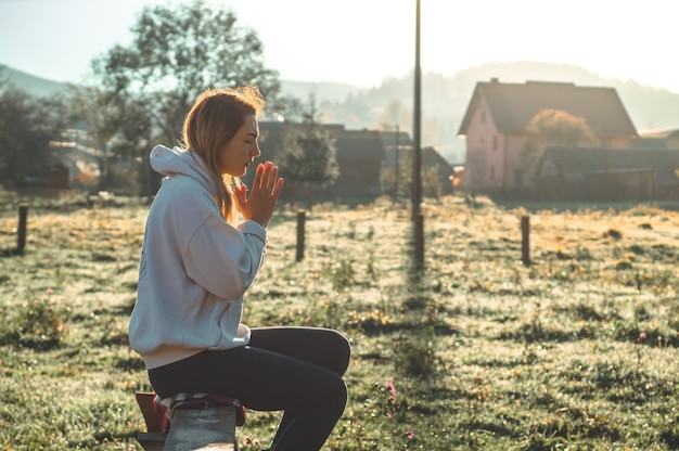 朝、少女は目を閉じ、屋外で祈り、手を組んで信仰、霊性、宗教のための祈りの概念がありました。平和、希望、夢のコンセプト。