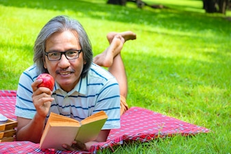 In the morning he is reading book with   red apply.He is  lying on the grass beside picnic
