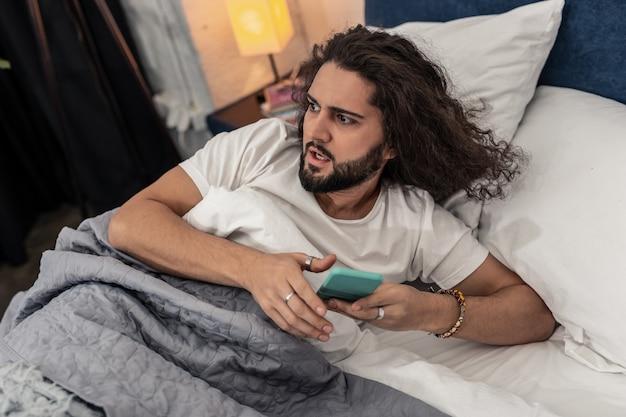 Утром. хороший длинноволосый мужчина держит смартфон, готовый встать