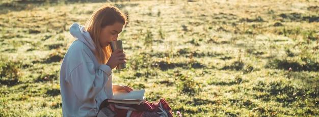 朝、女の子は山の中で木のベンチに座って本を読み、サーモカップから熱いお茶を飲みます。概念自然の中での読書。アウトドアトレーニング