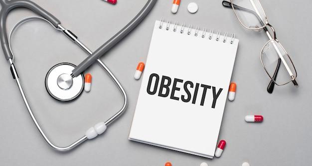 노트북에는 청진기, 알약 및 안경 옆에 obesity라는 텍스트가 있습니다.