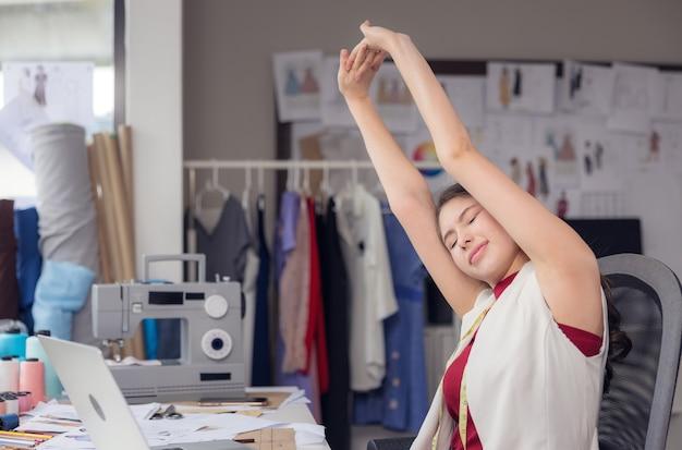 В офисе красивая азиатская женщина, стильный модельер, растягивается на столе, а молодая бизнесвумен пытается прийти в себя после долгого рабочего дня в магазине одежды.