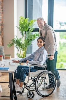 사무실에서. 장애가 있는 젊은 여성이 식탁에 오도록 돕는 남자