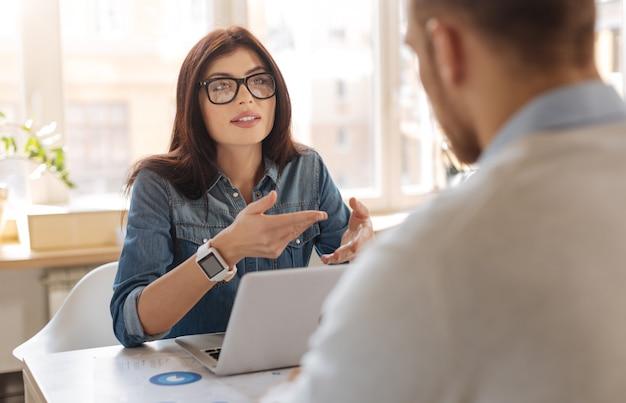В офисе. привлекательная умная приятная женщина сидит за столом и смотрит на своего коллегу, что-то ему объясняет