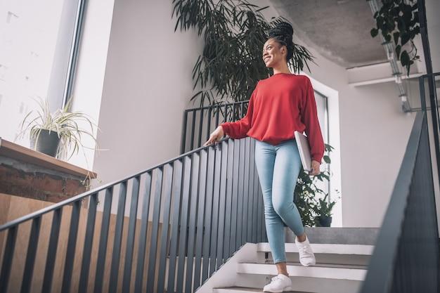 会社で。笑顔でオフィスを歩いているラップトップと赤いシャツを着た黒人女性