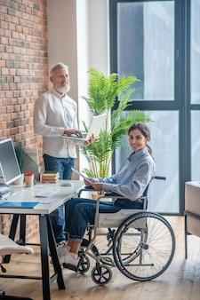 사무실에서. 사무실에서 테이블에 앉아 장애인된 젊은 여자